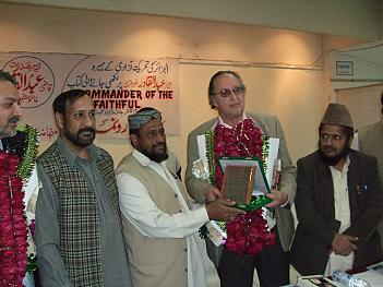 Author receiving plaque celebrating his book from Madrass leader Professor Afridi